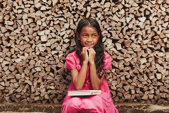 A girl in a pink dress sitting in front of a stack of wood