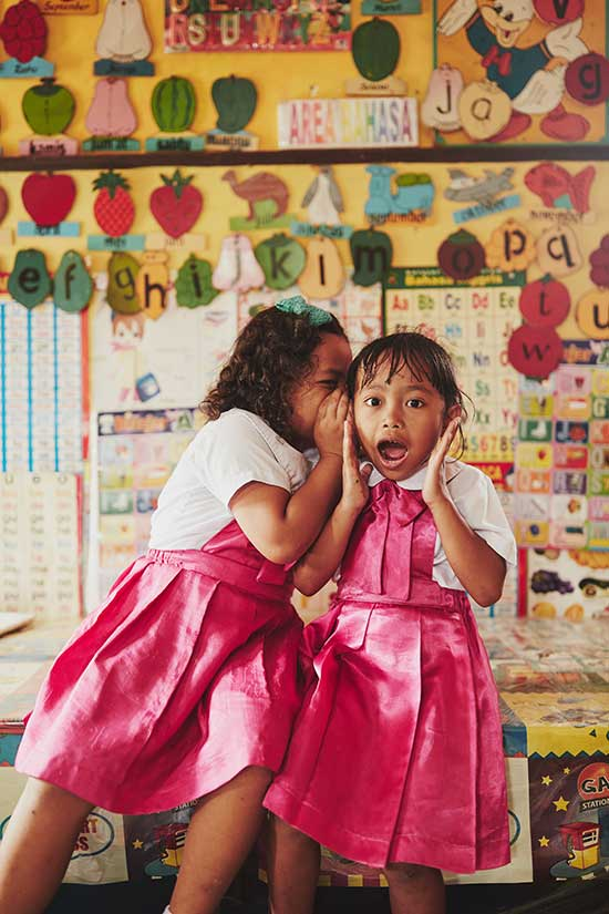 A girl in a pink dress whispers in the ear of another girl wearing a pink dress