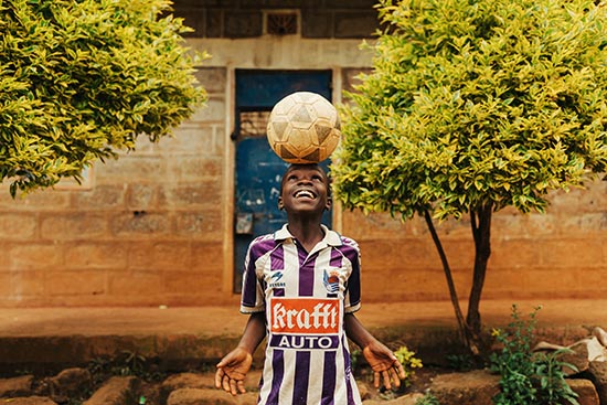 A boy in a soccer jersey balances a soccer ball on his head