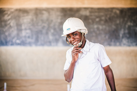 A boy wearing a white t-shirt and a white construction hard hat