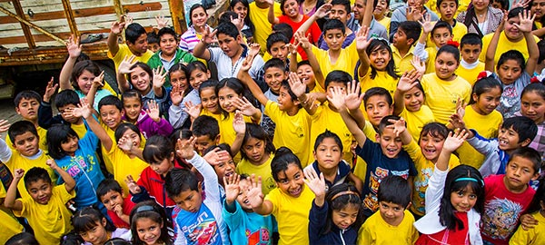 A large group of children waving hello
