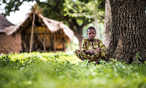 A boy squats down next to a tree