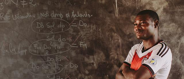 A male teacher stands in front of a chalkboard with his arms crossed