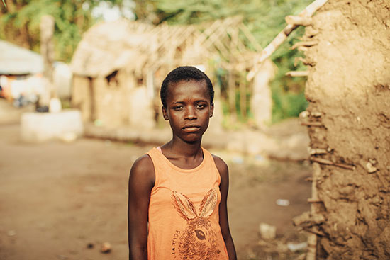 A solemn looking girl with an orange tank top on stands next to a mud hut