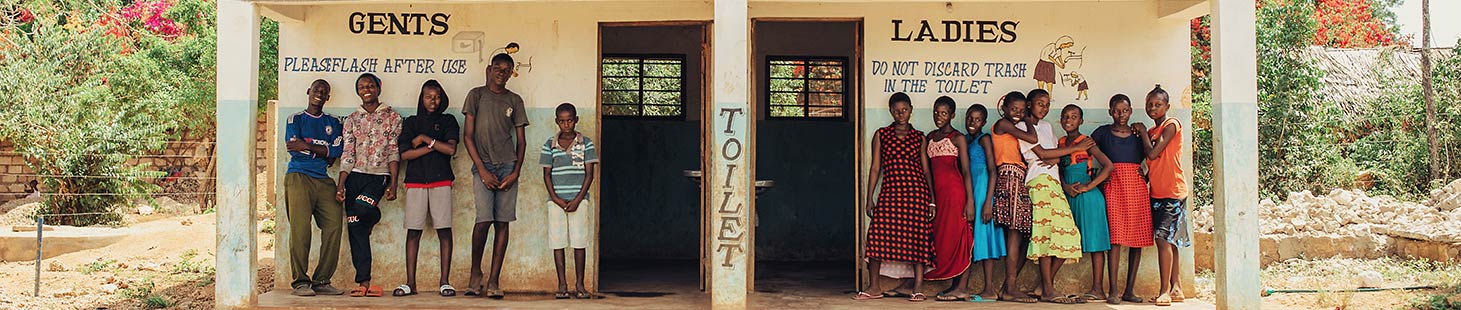 a group of young men and young women stand in front of a building with men's and women's hygienic toilets
