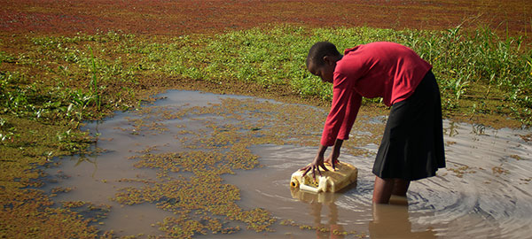 A woman in a red shirt bends at the waist to fill a jerry can with water from a pond