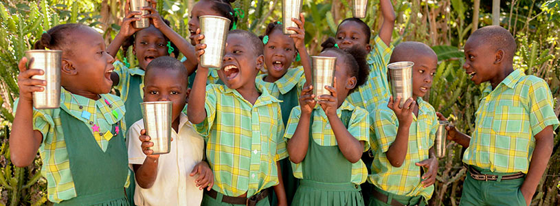 A group of young smiling and laughing Haitian children run hold cups of clean water in the air.
