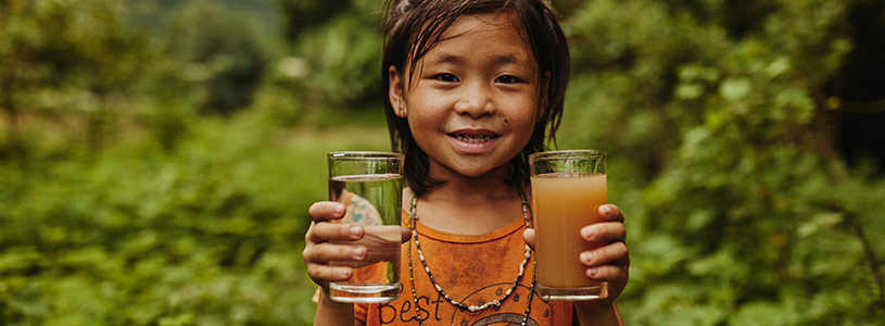 A young Thai girls holds up a glass of clean water and a glass of dirty water.