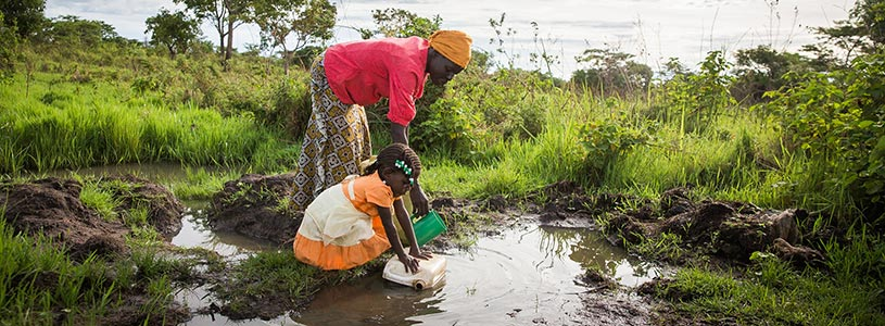 Two Ugandan women fill buckets with water from a pool of dirty standing water.