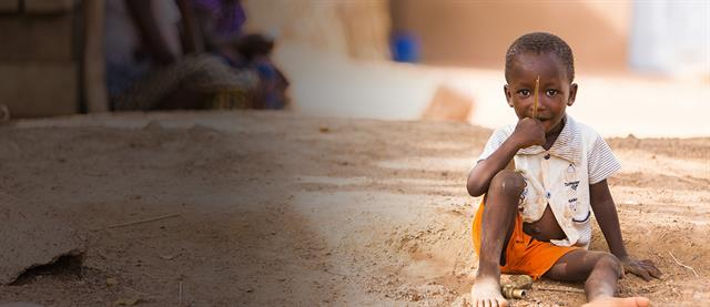 A young boy sits on a street in a poor country