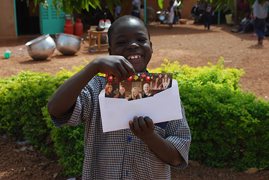 A boy in Burkina Faso opening a letter from his sponsor with pictures inside