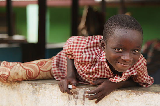 A boy in Ghana climbing over a wall