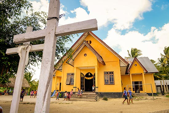 Two crosses in the front of a yellow church building
