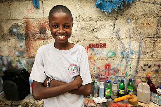 A young boy smiling with his arms folded