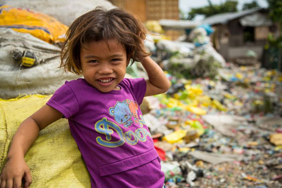Young girl smiling while standing near trash piles