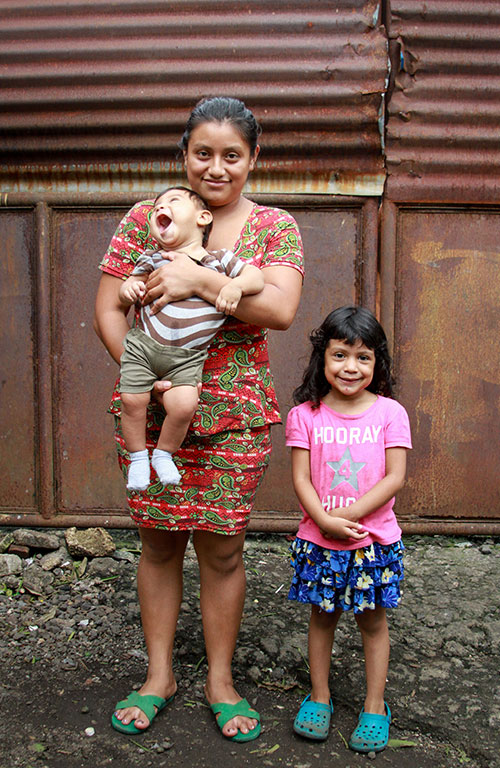 Maria with her two children outside their home in Guatemala