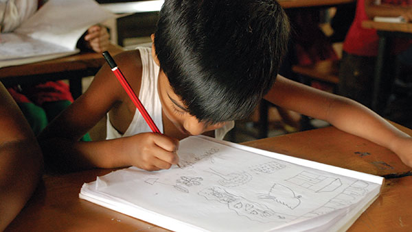 Bangladesh Boy Drawing in Notebook