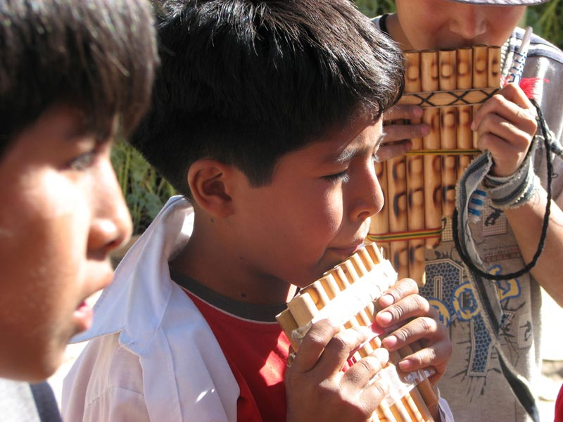 Bolivia boy playing flute