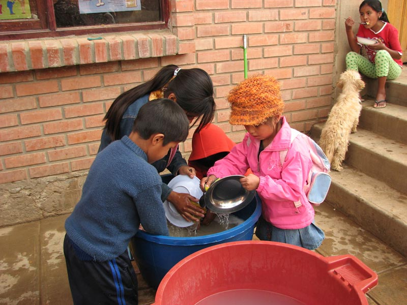 Bolivia children washing dishes