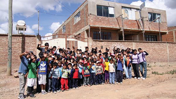 Bolivia children waving outside center