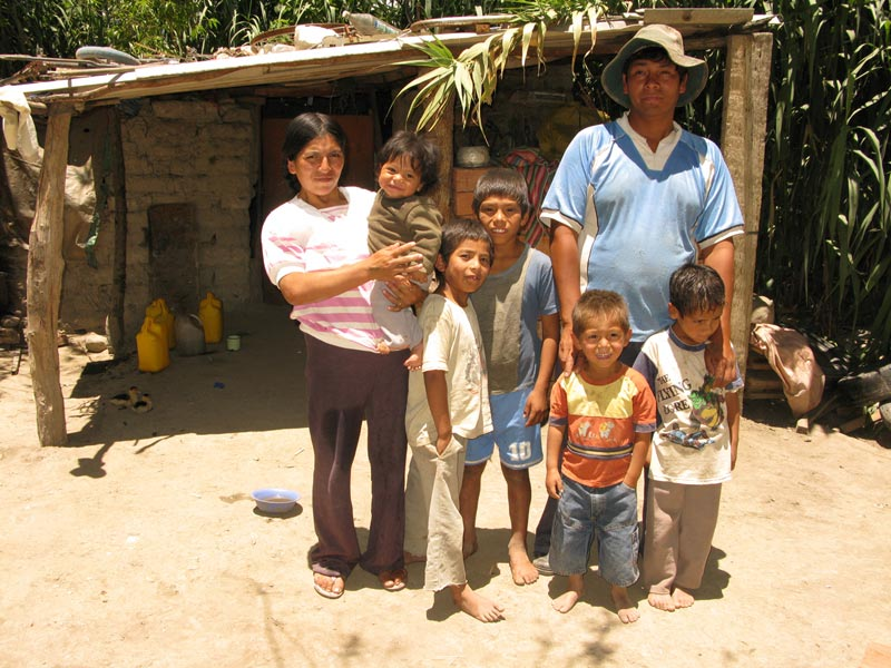 Bolivia family standing in front of home