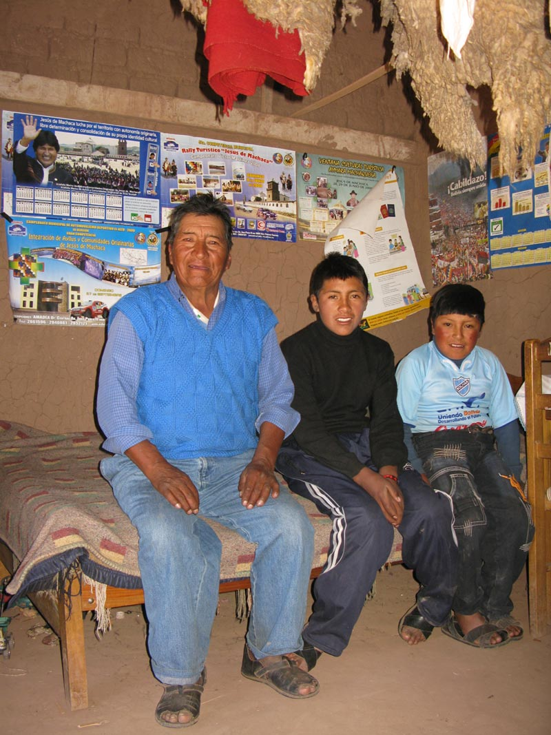 Bolivia father and sons sitting on bed
