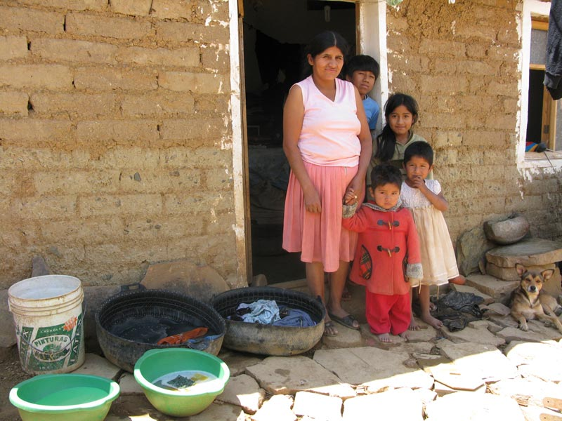 Bolivia mother and children in doorway of home