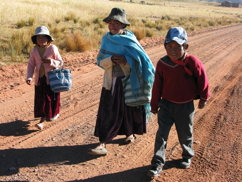 Bolivia woman and children walking on road