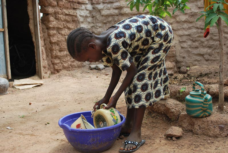 Burkina Faso Girl Washing Dishes