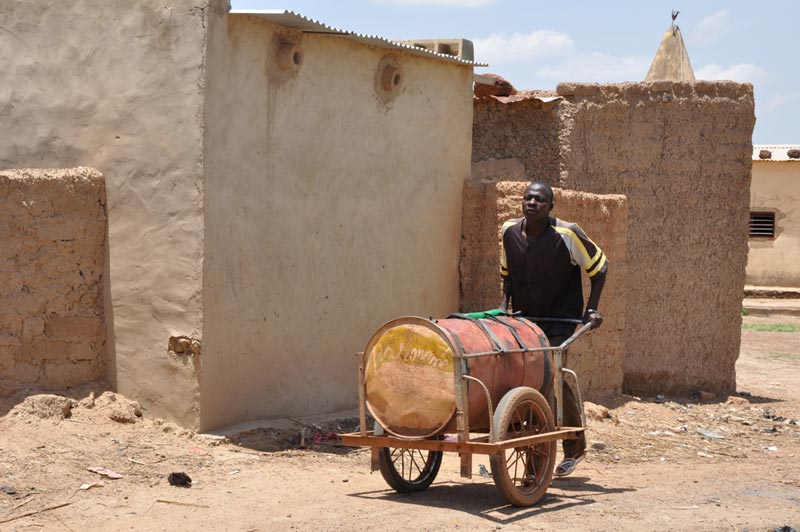 Burkina Faso Man Pushing a Barrel