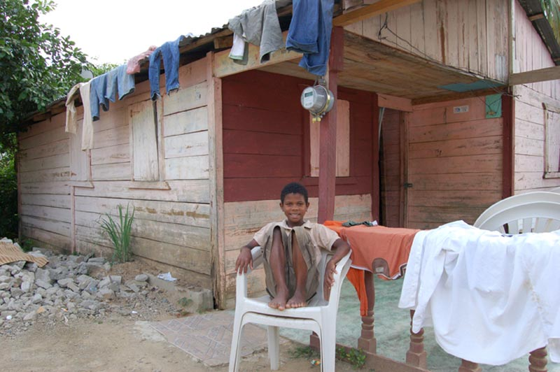 Dominican Republic Boy Sitting in Front of Home