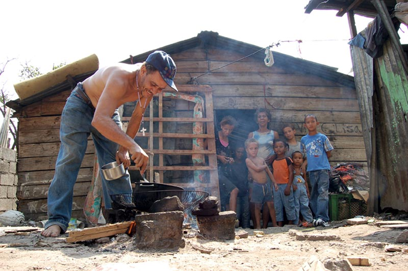 Dominican Republic Man Cooking in Front of His Home