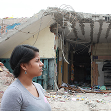 A woman stands in front of a fallen building after an earthquake in Mexico