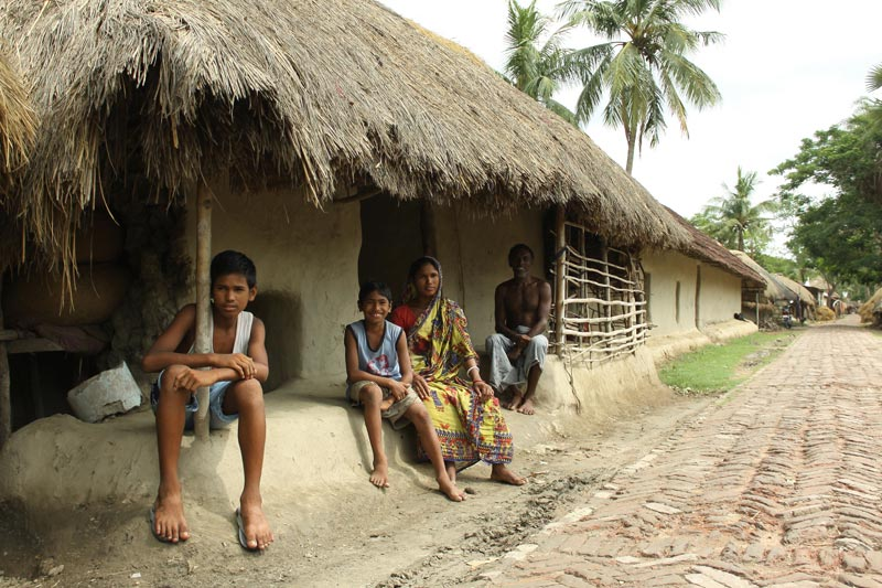 East India family sitting outside home