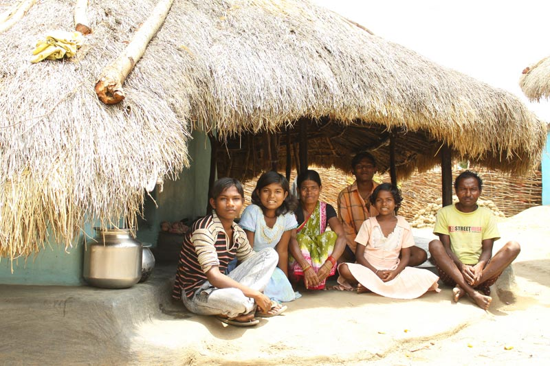 East India family sitting under thatched roof