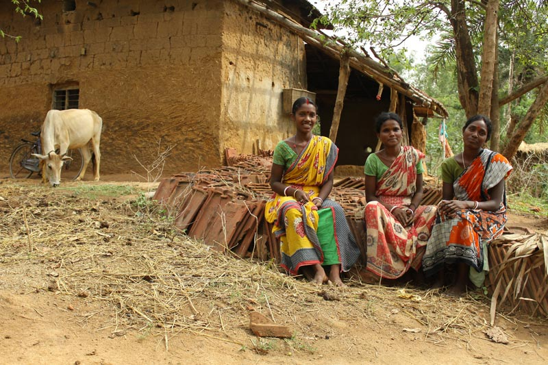 East India Women Sitting Outside of a Home