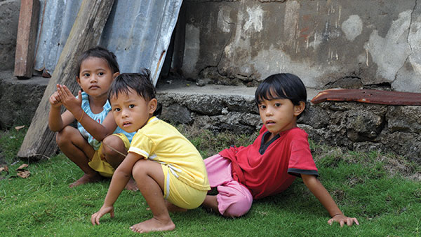East Indonesia children sitting in grass