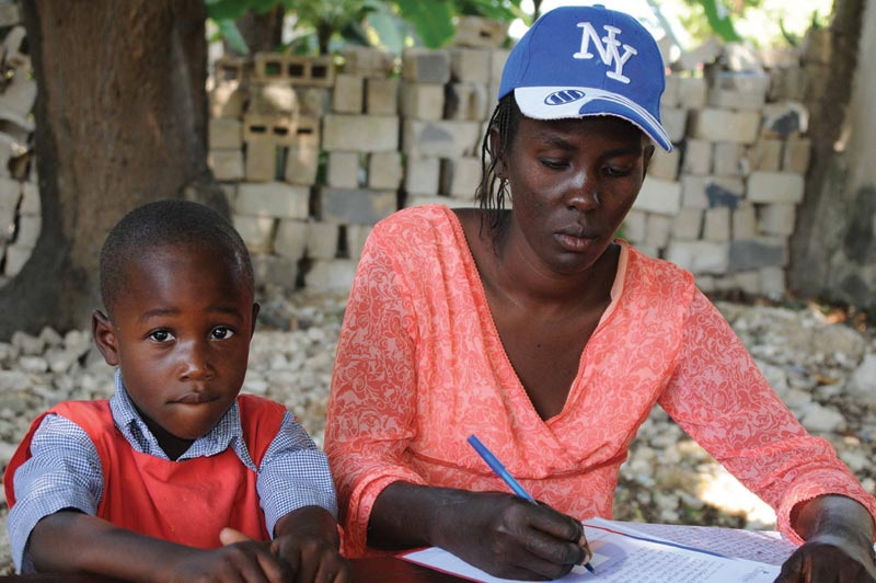 Haiti Woman and Young Boy Writing Letter