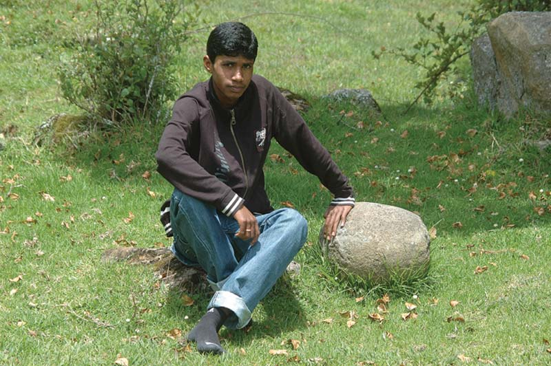 India boy sitting on rock