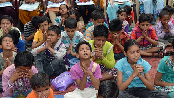 India children praying in a group