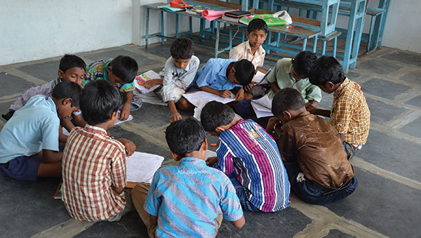 India children studying on floor