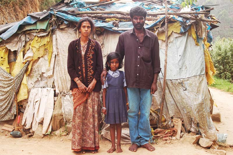 India family outside small home