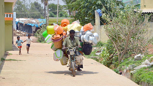 India man carrying buckets on motorbike