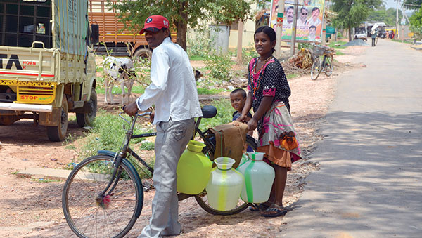 India man carrying water on bike