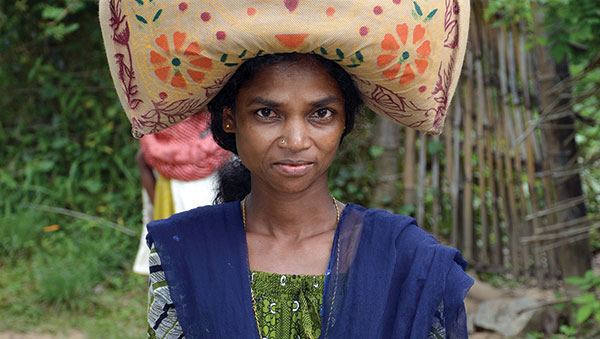 India woman carrying bag on head