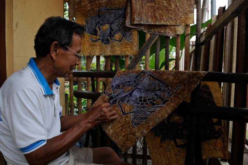 Indonesia man painting tapestry