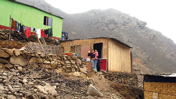 Peru Woman and Child Outside of Their Home on a Hill
