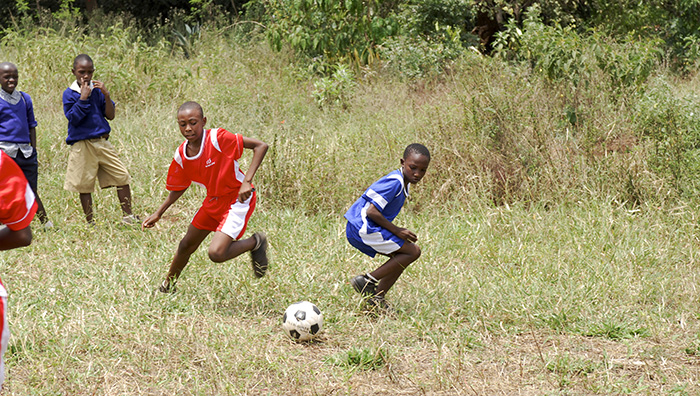 Tanzania Boys Playing Soccer Wearing Red and Blue Jerseys