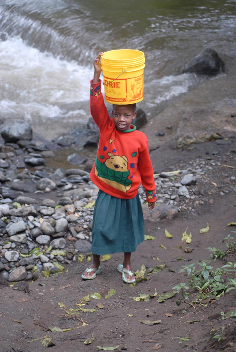Tanzania Girl Carrying Bucket on Head