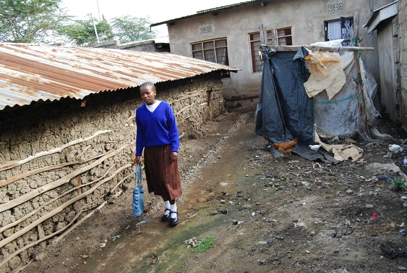 Tanzania Girl Walking Between Homes